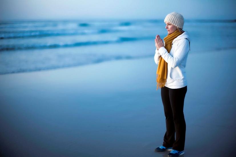 Uma rapariga em meditação na praia: o Reiki proporciona conforto e paz interior | Foto: Christopher Michel/Creative Commons