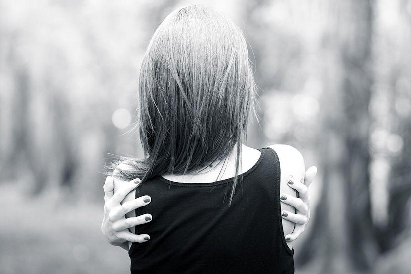Uma rapariga abraçada a si própria: com o Reiki é possível cuidar de si mesmo | Foto: Stefano Montagner/Creative Commons