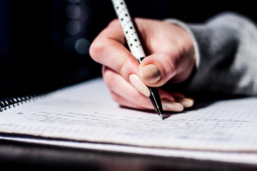 Uma mão a tirar notas sobre um caderno: os estudantes são das populações mais vulneráveis ao stress | Foto: Pexels