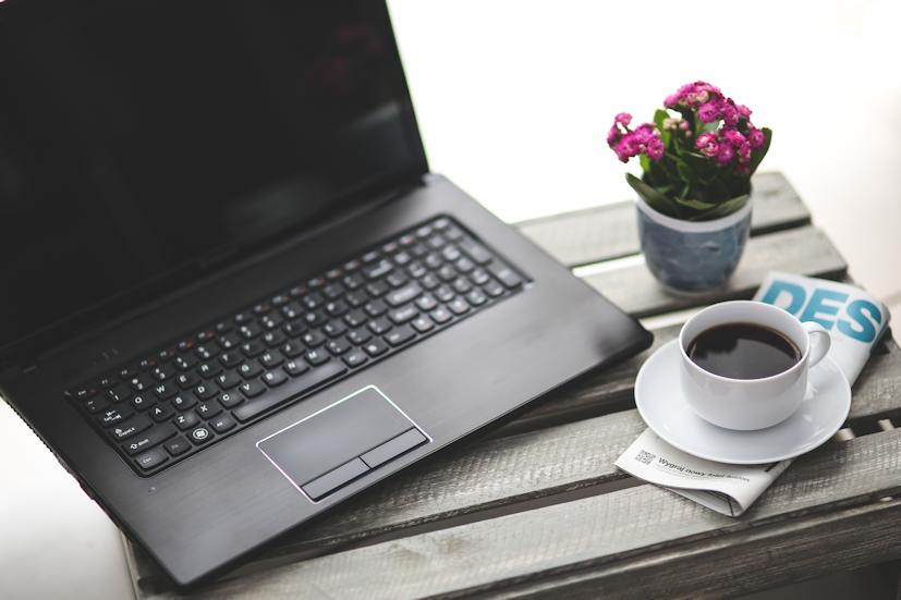 Um computador, uma revista e uma chávena de café: aproveite um momento de relaxamento para pesquisar um pouco sobre o Reiki | Foto: Pexels